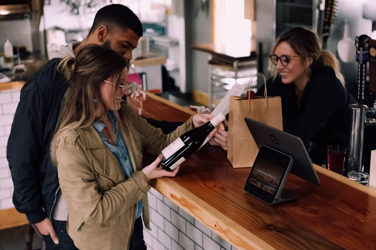 couple purchasing wine on romantic vacation