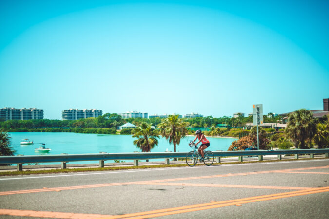 woman riding her bike on the Lido Key bridge