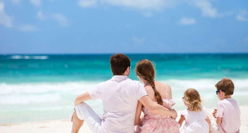 family of four sitting on beach watching ocean