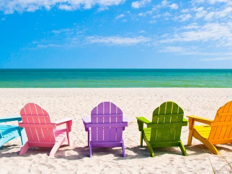 colorful beach chairs lined up on beach facing ocean