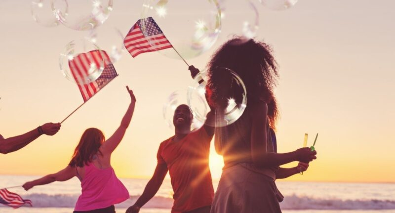 people waving flags and blowing bubbles on the beach