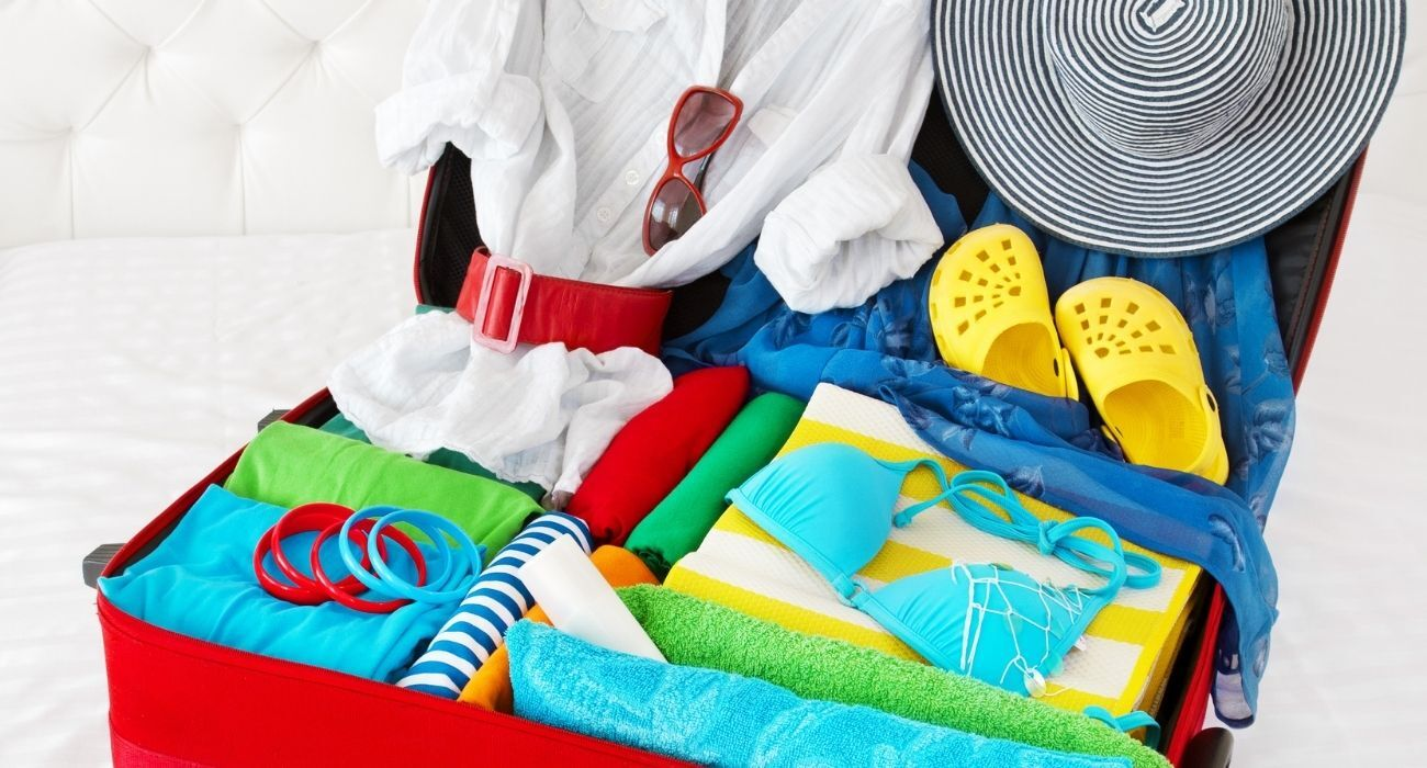 packed open suitcase full of summer outfits