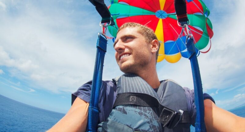 man taking a selfie while up in air parasailing