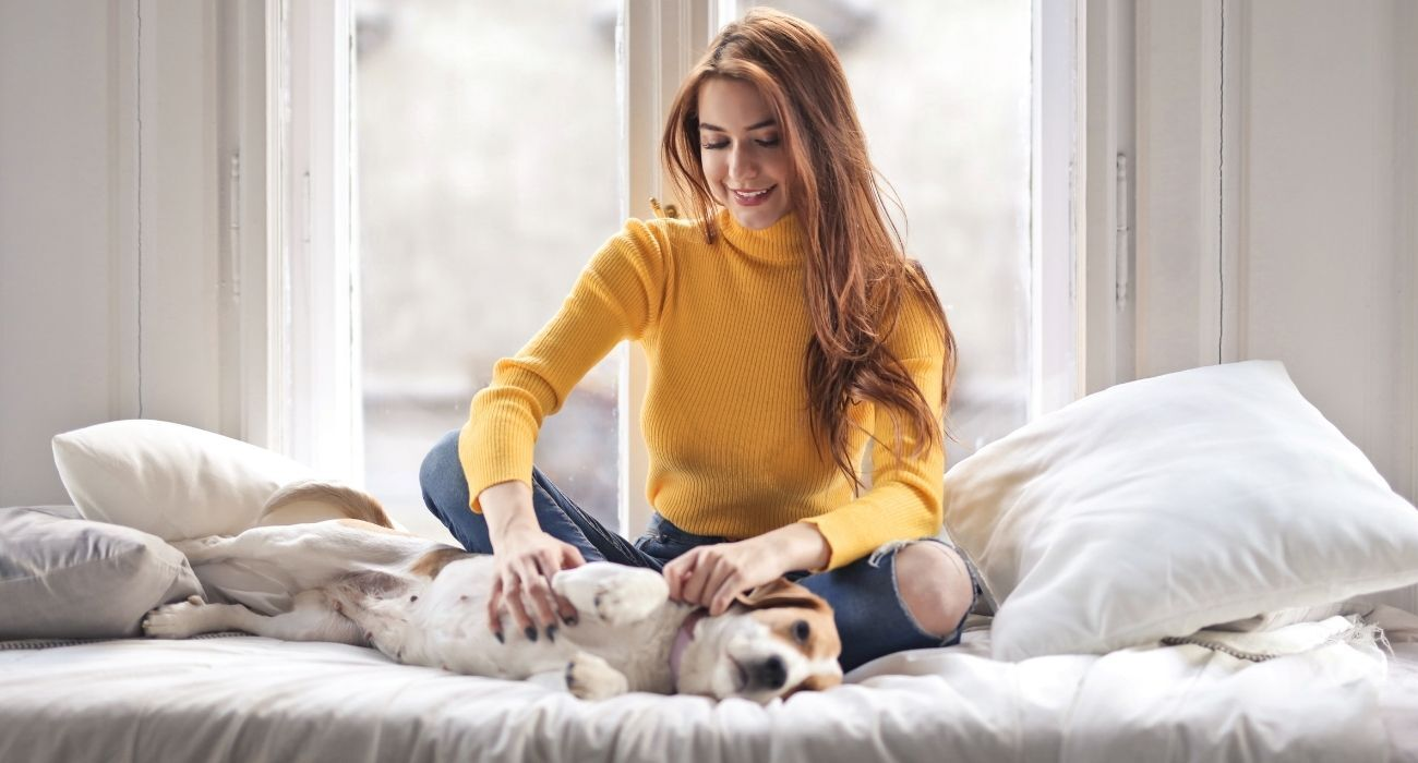 woman and her dog on bed
